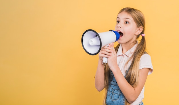 Girl child screaming through megaphone standing against yellow background