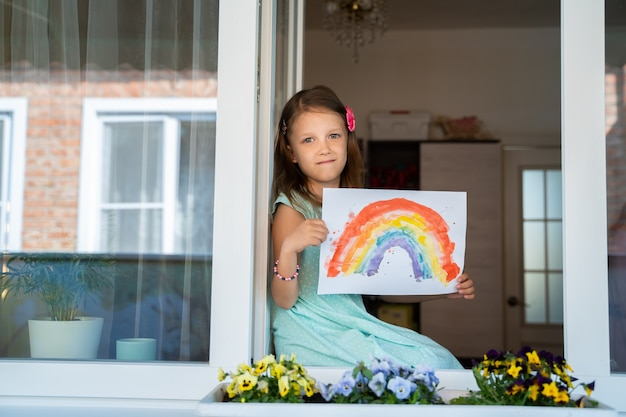 코로나바이러스 전염병으로부터 집을 격리하면서 손에 무지개 무늬가 있는 창밖을 바라보고 앉아 있는 여자 아이