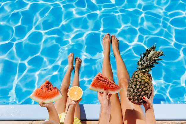 Girl and child sitting by the pool with tropical fruits in their hands