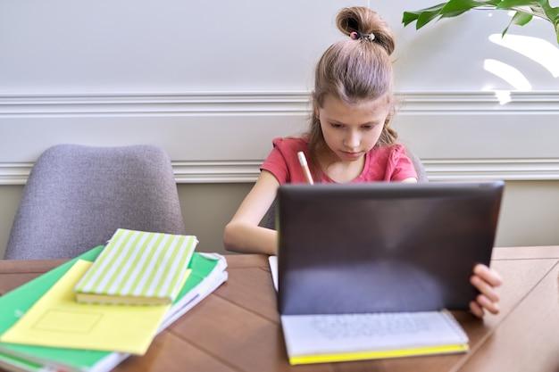 デジタルタブレットを使用して自宅で勉強している女児。遠隔教育、オンラインレッスン、ビデオ会議、電子形式の学校レッスン。現代の学校、技術、教育、子供の概念。