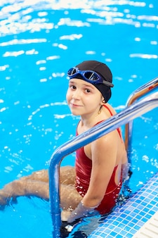 Girl child swimmer in a red bathing suit on background