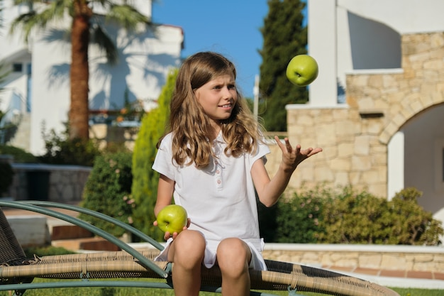 Girl child tossing, playing, juggling green apples, sitting on outdoor chair on green lawn
