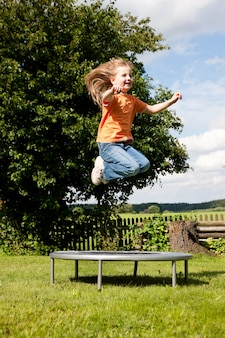Girl child on trampoline in the garden