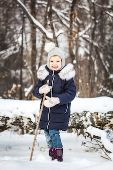 Girl child walking in the winter forest in a blue jacket and gray hat