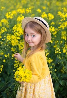 女児が畑を歩き、帽子をかぶって花、美しい笑顔、菜種畑を集める