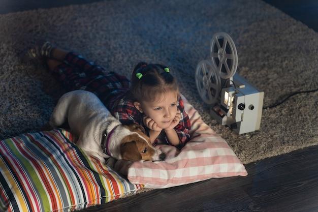 Девочки смотрят старый фильм на ретро винтажном кинопроекторе с собакой