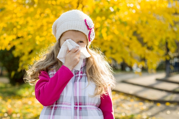 Girl child with cold rhinitis on autumn background