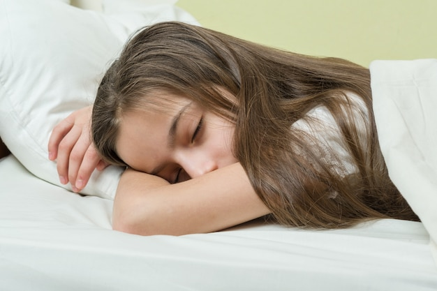 Girl child with long brown hair sleeping on pillow