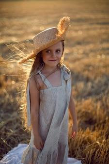 Девочки с длинными волосами гуляют по полю в шляпе с длинными волосами во время заката