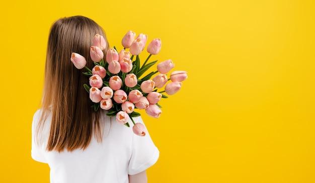 子供のコピースペースの後ろの肖像画と黄色の背景に分離されたピンクのチューリップの花を持つ女児...
