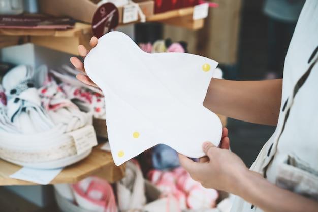 소녀는 플라스틱 무료 매장에서 천 생리 패드를 선택합니다. 폐기물 제로 매장에서 재사용 가능한 여성 패드