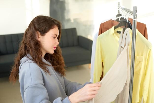 Девушка выбирает одежду и думает, что носить в домашнем гардеробе