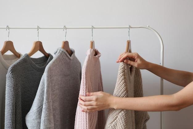 Девушка выбирает теплый свитер из гардероба вешалки