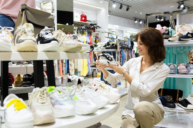 Girl chooses to buy sneakers for herself in a boutique