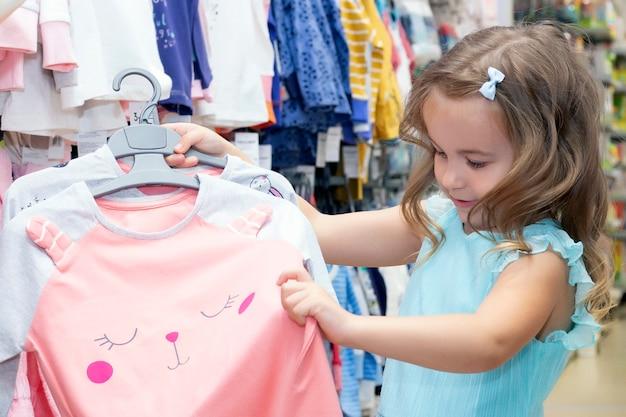 Девушка выбирает одежду в магазине одежды.