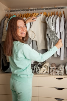 The girl chooses her clothes in the closet. a neatly organized wardrobe. items stacked vertically in baskets. clothes storage.