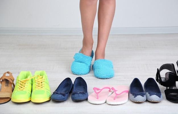 여자는 회색 표면에 방에 신발을 선택