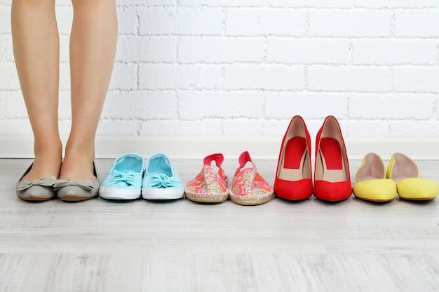 女の子は灰色の部屋で靴を選ぶ