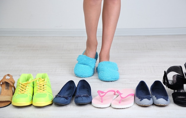 Girl chooses shoes in room on grey surface