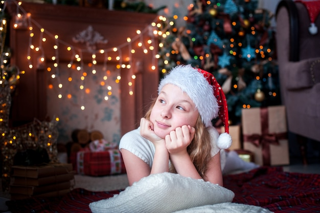 Girl in christmas cap lies on of fireplace and christmas tree bright