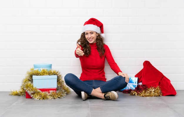 Girl in christmas holidays sitting on the floor handshaking after good deal