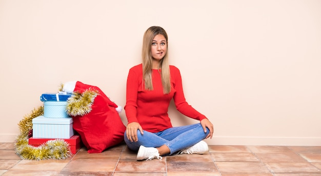 Girl in christmas holidays sitting on the floor having doubts and with confuse face expression