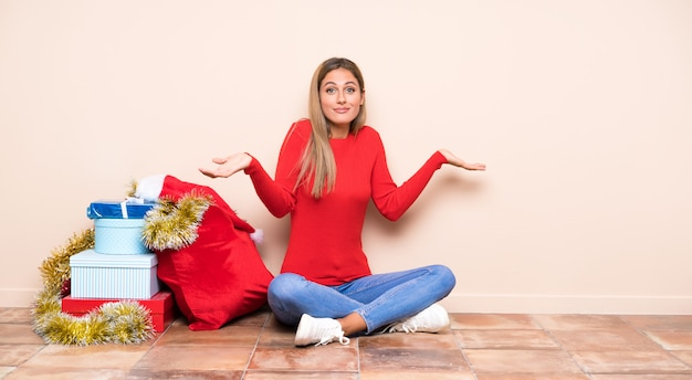 Girl in christmas holidays sitting on the floor having doubts with confuse face expression