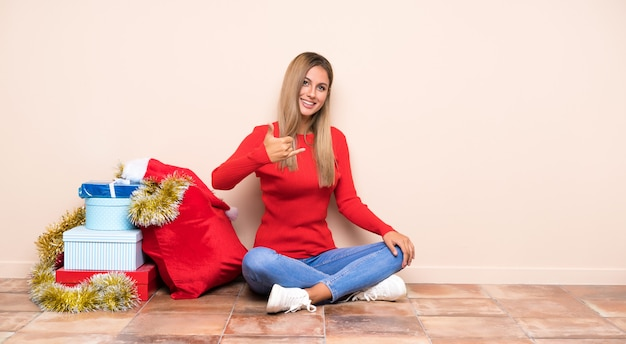 Girl in christmas holidays sitting on the floor making phone gesture
