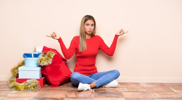 Girl in christmas holidays sitting on the floor pointing to the laterals having doubts
