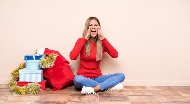 Girl in christmas holidays sitting on the floor shouting with mouth wide open