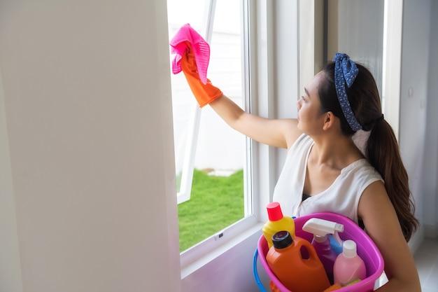 Девушка чистит окно из микрофибры