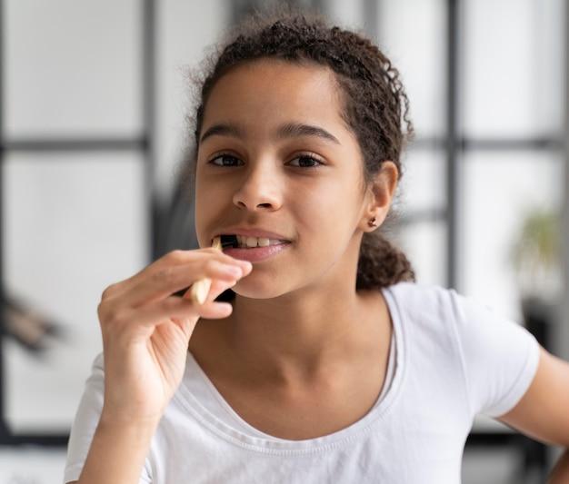 Girl cleaning her teeth before school