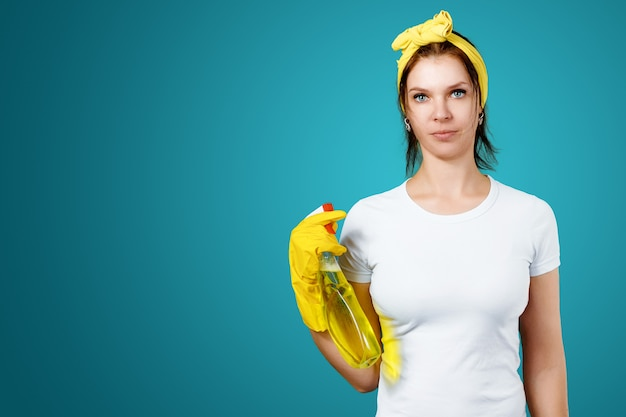 A girl a cleaning lady with a cleanser wearing gloves and a rag