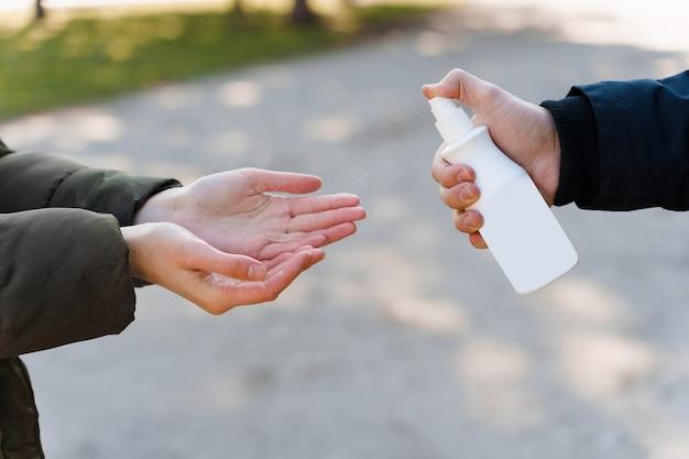 女の子はスプレー消毒剤で彼女の手をきれいにします