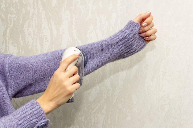 The girl cleans a knitted wool sweater with a electric fabric shaver to remove pellets, small lumps that have piled on the surface of clothing