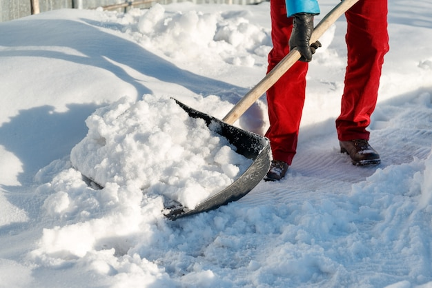 Girl cleans snow shovel on the site near his house. sunlight