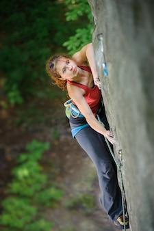 Girl climber climbing steep boulder, searching for next grip