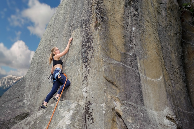 Girl climber climbing with rope and carabiners on a big boulder