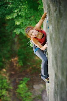 Girl climber looking for next grip on challenging rock wall