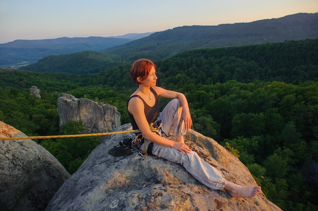 Girl climber on mountain peak on high altitude in evening