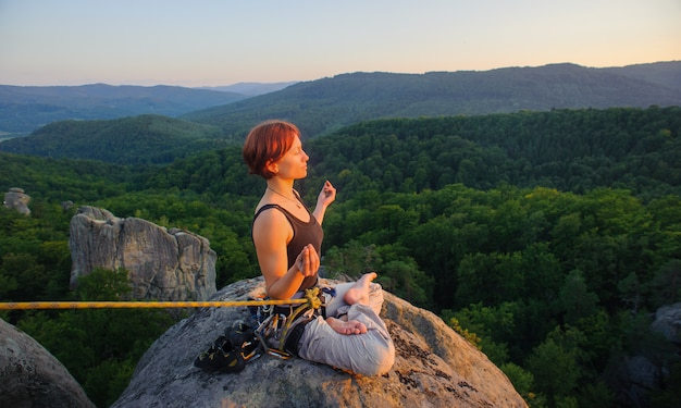Girl climber sitting secured with rope and meditating with crossed legs on high mountain summit