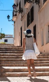 여름에 모자 셔츠 스커트와 흰색 가방을 들고 오래된 거리를 따라 계단을 뒤로 오르는 소녀