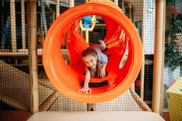 Девушка, поднимающаяся по лабиринту в детском игровом центре