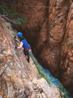 Girl climbing on a via ferrata, sant feliu de guixols, catalunya, spain