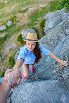 女の子は愛する人の手の助けを借りて岩に登る