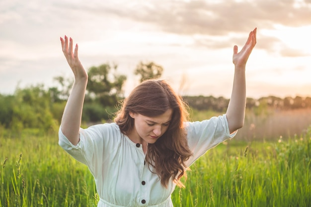 Girl closed her eyes, praying in a field during beautiful sunset