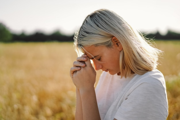 Girl closed her eyes, praying in a field. hands folded in prayer concept for faith.