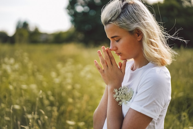 Girl closed her eyes, praying in a field.  hands folded in prayer concept for faith