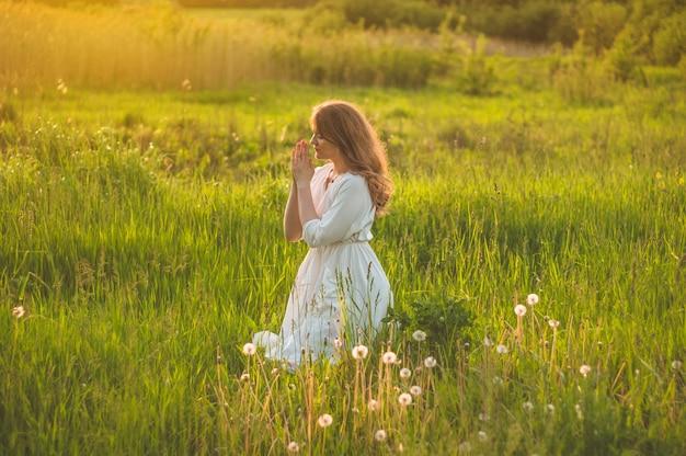 美しい日没時にフィールドで祈る少女は目を閉じた