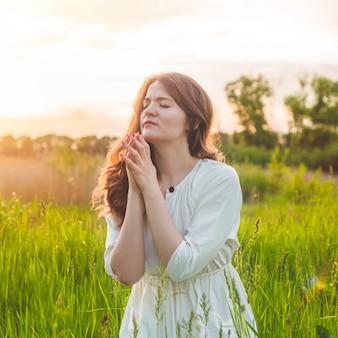 Девушка закрыла глаза, молясь в поле во время красивого заката